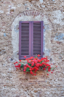 Scenic window in the medieval architecture of san gimignano, iconic town in the province of siena, and one of the most visited place in tuscany