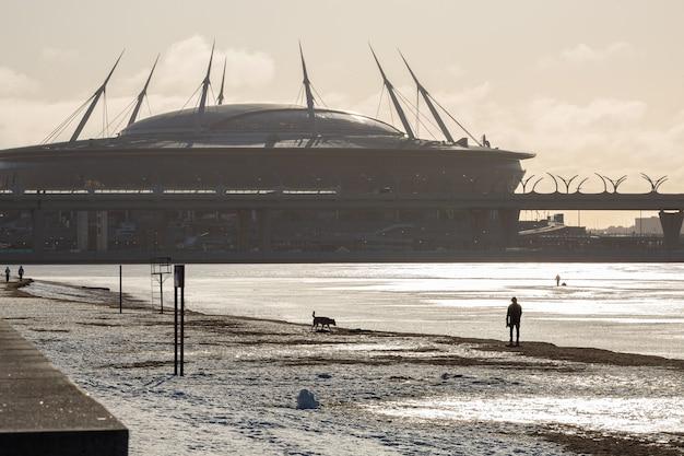 Живописное зимнее морское побережье парка 300-летия и огромный стадион, на котором фигурка человека гуляет с собакой.