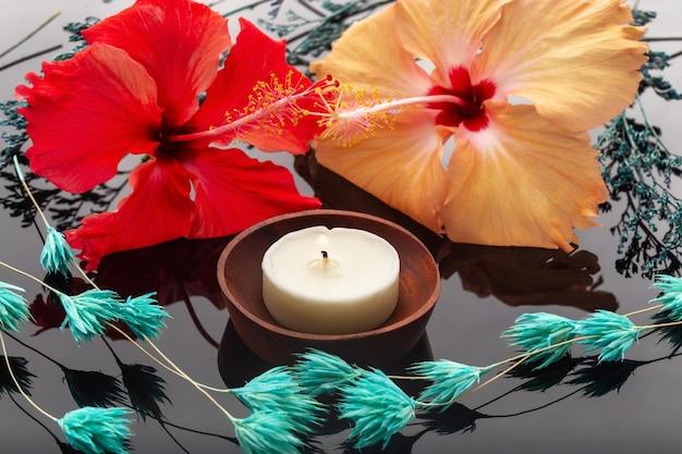 香りのキャンドル、黄色と赤の花-スパとアロマテラピー用に設定