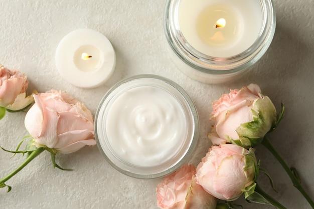 Ароматические свечи, косметический крем и розы на белом столе