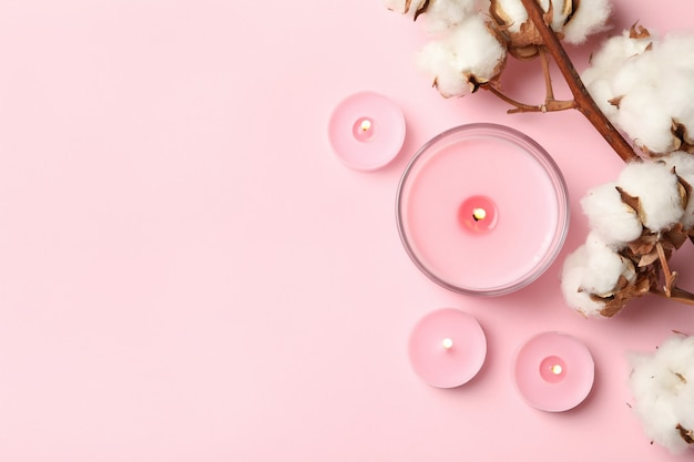 Scented candles and cotton on pink background