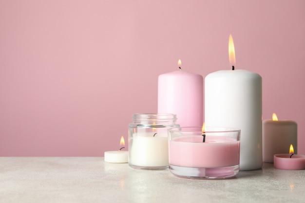 Ароматические свечи для отдыха на белом столе на розовом фоне