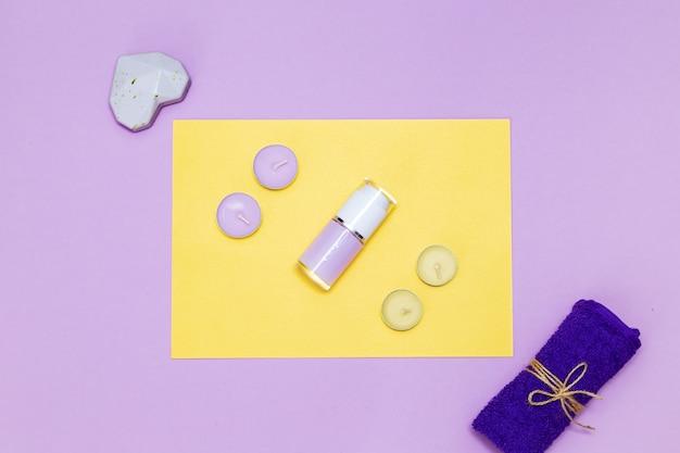 黄色と紫の背景に香りのキャンドル、タオル、ローション。上面図、コピースペース。スパのコンセプト、フラットレイ。