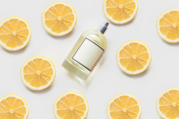 Scented oil or perfume, on a white wall, decorated with patterns of lemon slices. the concept of aromatherapy, or body care, citrus scents.