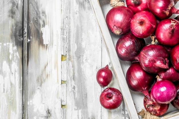 トレイに香りのする赤玉ねぎ。木製のテーブルの上