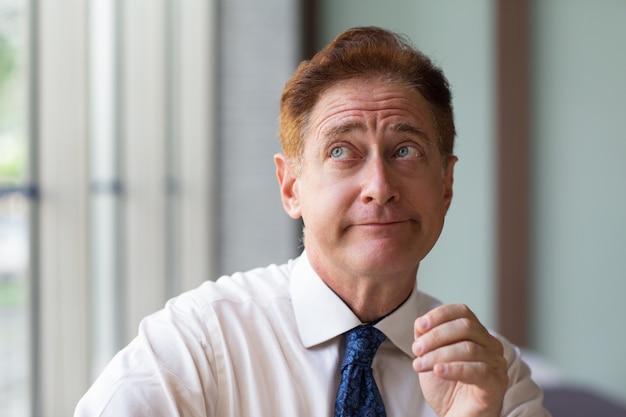 Uomo d'affari scettico alzando lo sguardo