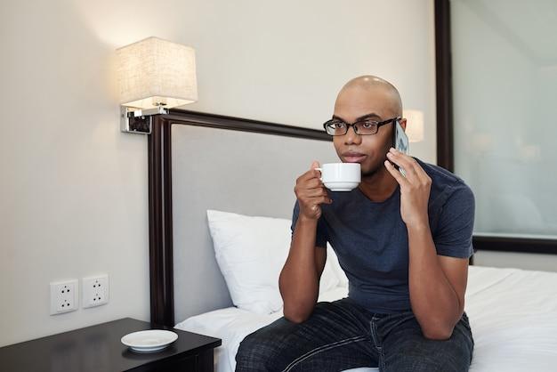 朝のコーヒーを飲み、同僚やクライアントと電話で話している眼鏡をかけた懐疑的な若いアフリカ系アメリカ人の男