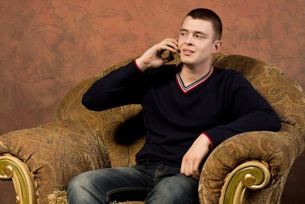 彼の携帯電話で話している懐疑的な若い男