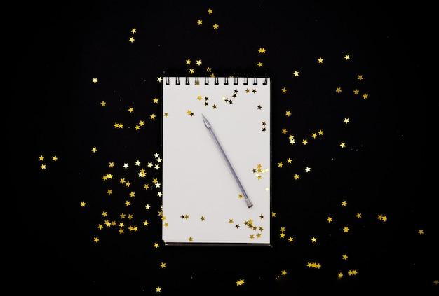 金色の星紙吹雪と黒の抽象的な背景に白のscetchbook。水平トップvi