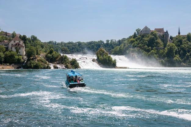Шаффхаузен, швейцария - 20 июня 2017 г .: посмотрите на рейнский водопад - самый большой водопад в европе и людей на лодке вокруг него. летний день с голубым небом