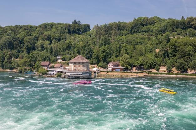 Шаффхаузен, швейцария - 22 июня 2017: лодка с людьми, плывущими к водопаду рейнский водопад. это одна из главных туристических достопримечательностей. летний день с голубым небом