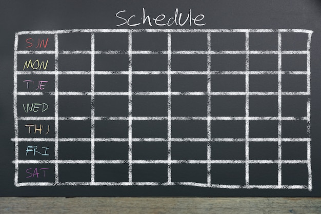 Schedule with grid time table on black chalkboard