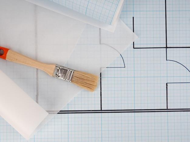 수리 및 디자인의 브러시 빌더 개념 근처 롤에 밀리미터 종이에 그리기 아파트의 개략도 계획. 주택 계획, 아늑한 주택, 건물 건설, 새 건물.