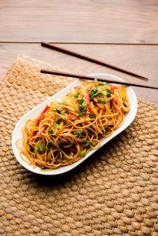 Лапша щезван или овощная лапша хакка или чау-мейн - популярный индокитайский рецепт, который подают в миске или тарелке с деревянными палочками для еды. Premium Фотографии