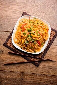 Лапша щезван или овощная лапша хакка или чау-мейн - популярный индокитайский рецепт, который подают в миске или тарелке с деревянными палочками для еды.