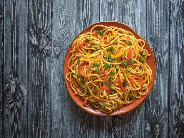 木製テーブルの上の皿に野菜とschezwan麺。上面図。客家麺は人気のあるインドシナのレシピです。