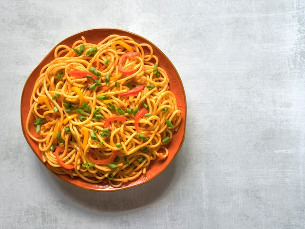 Schezwan noodles with vegetables in a plate. top view.