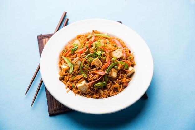 Жареный рис schezwan paneer с сычуаньским соусом и кубиками творога. подается в миске, тарелке или сковороде. выборочный фокус