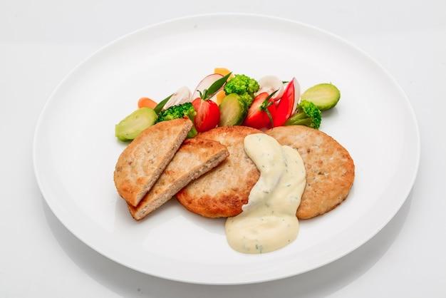 Шницель, куриная котлета с белым соусом и овощами, на белом фоне