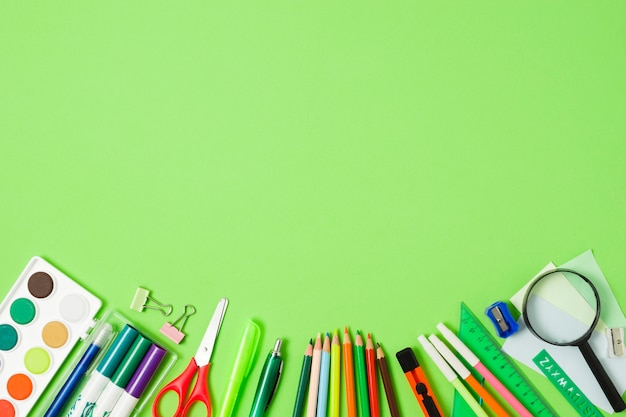 School accessories arrangement on green background