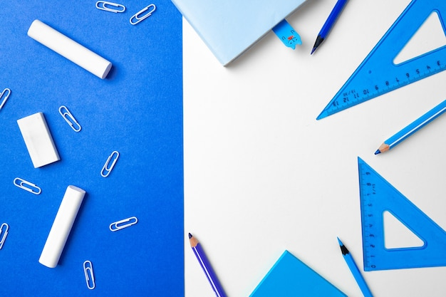 School accessories on blue and white background copy space