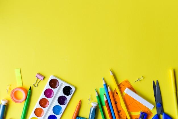Школьные принадлежности на желтом фоне. скопируйте пространство. снова в школу творческой плоской планировки.