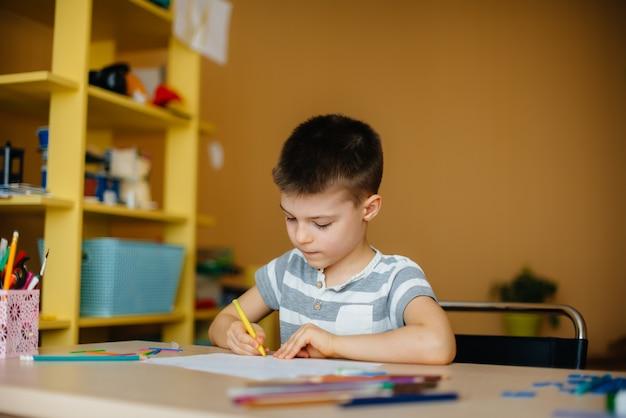 School-age boy does homework at home. training at school