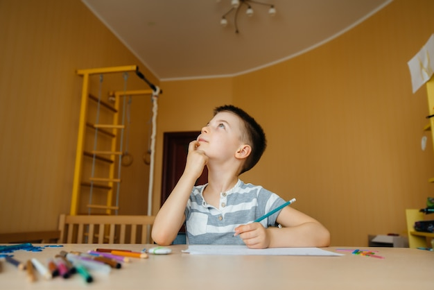 A school-age boy does homework at home