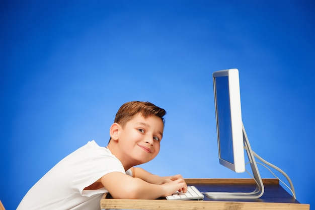 School-age boy sitting in front of the monitor laptop