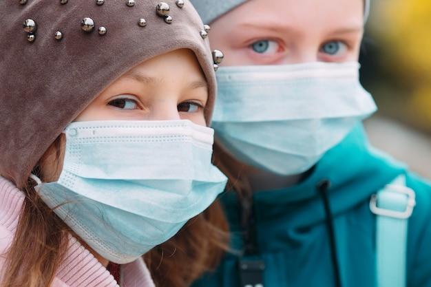 医療用マスクの学齢期の子供たち。学童の肖像画。