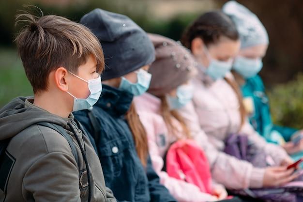 医療マスクの学齢期の子供たちはベンチに座っています。
