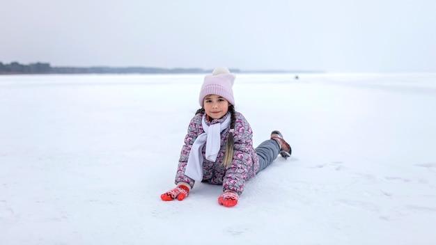 学齢期の女の子は凍った湖で楽しんで、冬の季節を楽しんでいます。冬、沈黙と野生の自然、活発な冬の週末、季節の野外活動、幸せな家族のライフスタイル、コピースペース