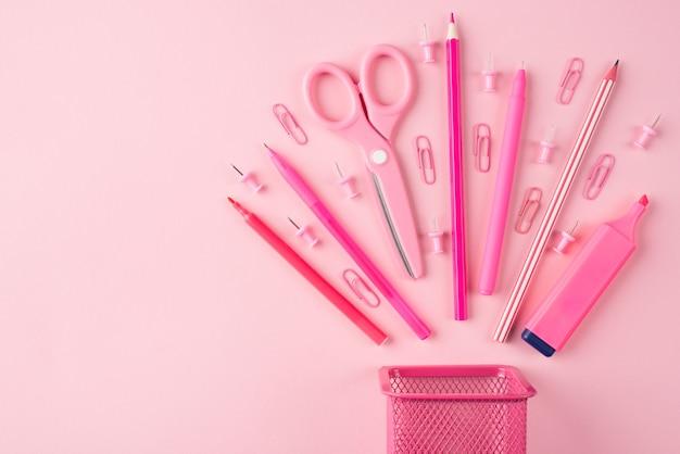학교 및 사무실 문구 개념입니다. 복사 공간이 있는 파스텔 핑크 배경에 격리된 오른쪽에 배치된 분홍색 편지지의 오버헤드 뷰 사진 위