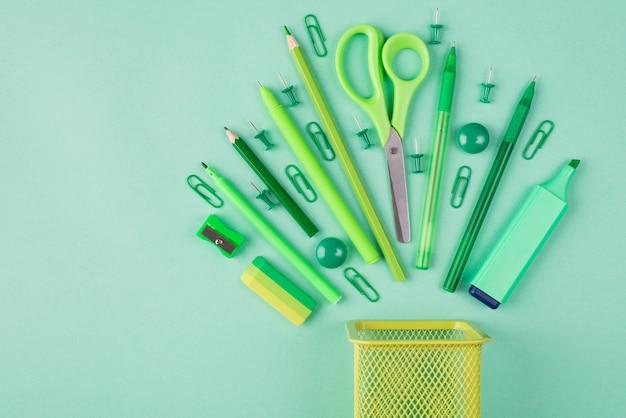 학교 및 사무용품 개념입니다. 청록색 배경에 고립 된 녹색 정렬 편지지의 오버 헤드보기 평면 사진 위의 상단