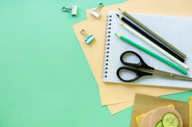Школьные и офисные принадлежности на фоне мяты. пространство для текста