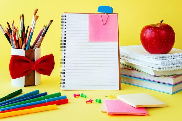 Школьные и офисные принадлежности на столе класса на желтом