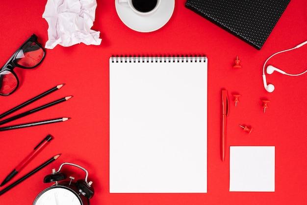メモ、ペン、鉛筆、電卓、ブラシ、はさみ、コーヒー、ラップトップなどの学用品や事務用品は、赤い背景の上にきれいに横たわっています