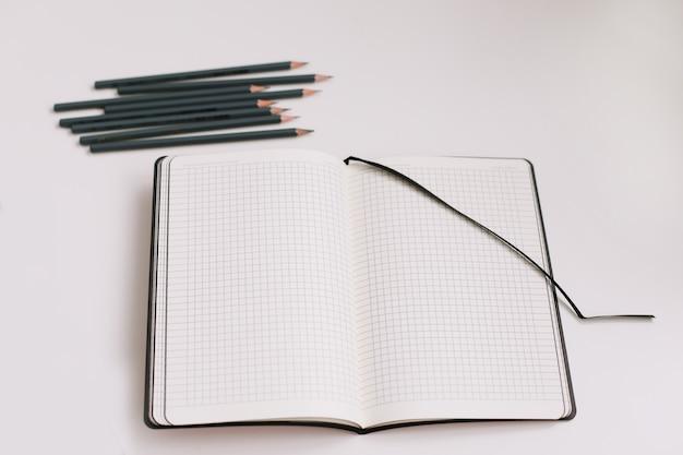 Школьные и офисные принадлежности вид сверху тетради и карандашей на белом фоне с копией пространства