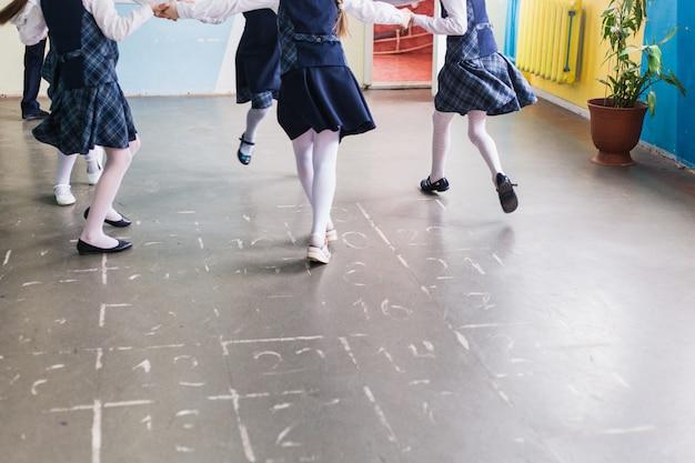 学校と学童、子供たちは休憩時間に走り、レッスンの合間に休み、子供の足、発達、ウォームアップ、スポーツ