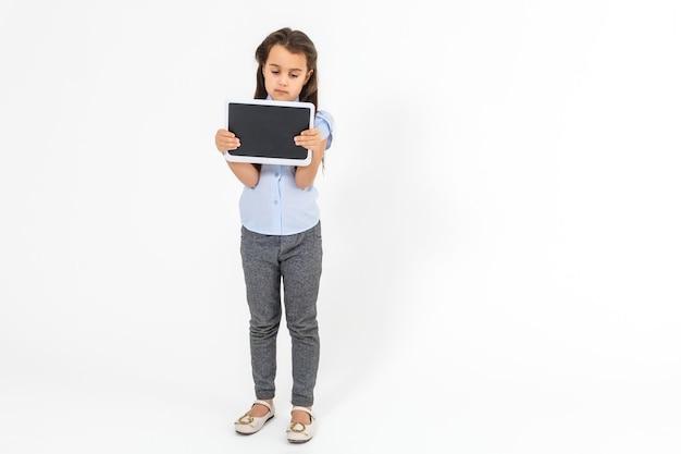 Школа и технологии. во всю длину довольно маленькая девочка, стоящая с рюкзаком, держащим планшет. изолированные на белом.