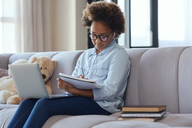 집에서 학교에서 공부하는 동안 이어폰을 끼고 노트북에 메모를 하는 십대 여학생
