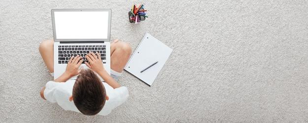 Школа дома через домашнее обучение онлайн. ребенок сидит за компьютером