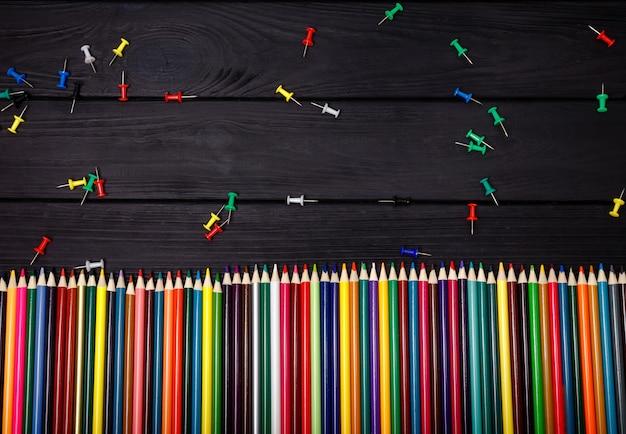 Школа фон. цветные карандаши на черном фоне. вид сверху, макет