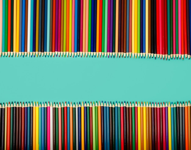 Школа фон. цветные карандаши на синем столе. вид сверху