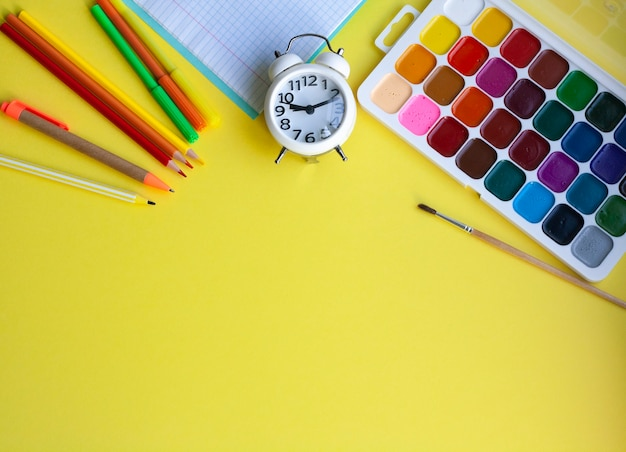 School background with school supplies on yellow, pen, pencils, markers, watercolors, notebook and alarm clock, flat lay, copy space