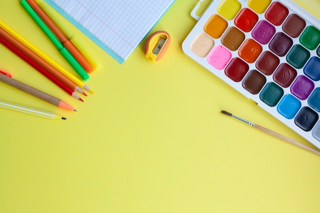 School background with school supplies on yellow, pen, pencils, markers, watercolors, notebook, sharpener, flat lay, copy space