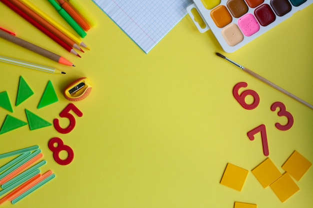School background with school supplies on yellow, pen, pencils, markers, watercolors, notebook, sharpener, numbers, geometric shapes, counting sticks, flat lay