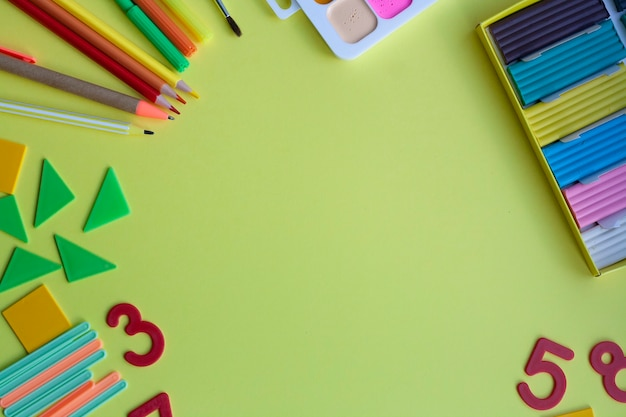 School background with school supplies on yellow, pen, pencils, markers, watercolors, plasticine, sharpener, numbers, geometric shapes, counting sticks, flat lay, copy space