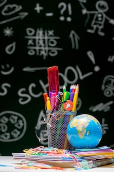 文房具の付属品と学校の背景。本、グローブ、鉛筆、緑の黒板背景に机の上に横たわる様々な事務用品