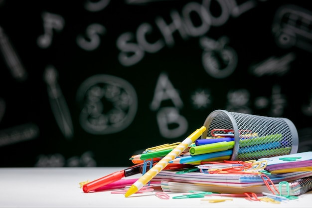 文房具アクセサリーと学校の背景。本、グローブ、鉛筆、緑の黒板背景に机の上に横たわる様々な事務用品